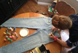 After buying a pair of mom jeans at Goodwill, Alli Harper, 10, decorates her jeans to fit her unique style with fabric paint. Photo by Maddie Baker