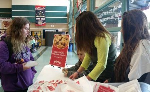 Seniors, Courtney Hughes, Lauren Abercrombie, and Caroline Teixeira, sell cookies during second lunch to Nicole Norad, 10. Photo by Saveria Farino