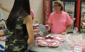 Purchasing a pink cupcake at the Dig Pink vollyball game, Andrea Yuen, freshman, shows her support for the cause. (Photo by Kacie Leach)