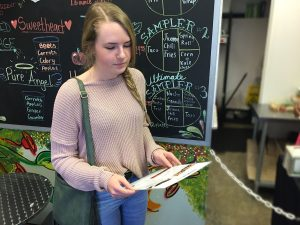 In front of the Simply Pure specials board, Kaylee Heiny, 10, scans the menu, pondering which of the vegan options she should eat for lunch. Photo by Sage Tippie