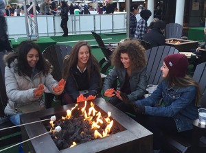 Taking a break from ice skating at The Ice Rink at the Cosmopolitan Hotel, freshmen Sage Tippie and Rayne Hayes and sophomores Saveria Farino and Regina Dispa, warm up their hands around the fire. Photo courtesy of Regina Dispa