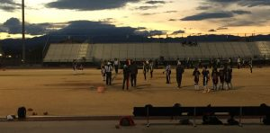 At the start of the game, the Cougars and Rattlesnakes face off for the first pike as the sun sets. Photo by McKenna Cooley