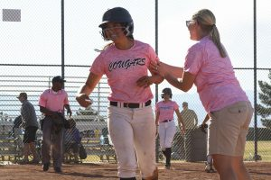 After running to home base during the Strike Out Cancer game, Taylor Okamura gets congratulated by Coach Krueger. Photo by Giana Haynia.